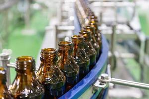 bottiglie di vetro su nastro trasportatore