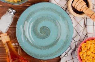 Vista dall'alto di diversi macaroni in ciotole sale pepe nero burro intorno alla piastra su sfondo di legno foto