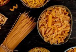 vista dall'alto di diversi tipi di maccheroni come cavatappi spaghetti vermicelli tagliatelle e altri su fondo in legno