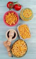 Vista dall'alto di diversi tipi di maccheroni come spaghetti cavatappi ziti con pomodoro sale pepe nero su sfondo di legno