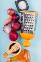 vista dall'alto di cipolle tagliate e intere con burro fuso, pepe nero, sale e grattugia su sfondo blu foto