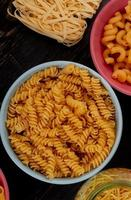 vista dall'alto di diversi tipi di maccheroni come rotini cavatappi spaghetti tagliatelle su fondo in legno