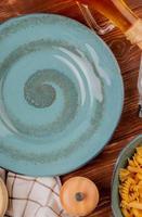 Vista dall'alto di diversi macaroni nella ciotola burro di sale intorno alla piastra su sfondo di legno foto