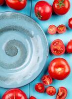 vista dall'alto di pomodori tagliati e interi intorno alla piastra su sfondo blu foto