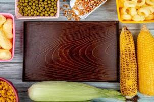 Vista dall'alto del vassoio vuoto con piselli semi di mais mais pop cereali e pannocchie di mais su sfondo di legno foto