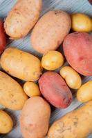 vista dall'alto di nuove patate rosse bianche e gialle ruggine su fondo in legno foto