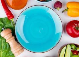vista dall'alto di verdure come pomodoro ravanello pepe con burro e lasciare con piatto vuoto su sfondo bianco foto