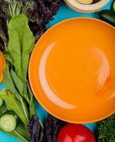 vista dall'alto di verdure come spinaci basilico cetriolo pomodoro con piastra su sfondo blu foto