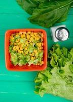 vista dall'alto della ciotola di piselli gialli con lattuga a fette e spinaci sale tutta la lattuga su sfondo verde foto