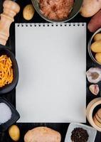 Vista dall'alto di patate grattugiate a fette e intere intorno al blocco note con sale pepe nero su sfondo di legno con spazio di copia foto