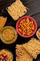 Vista dall'alto di diversi tipi di maccheroni come bucatini cavatappi spaghetti vermicelli tagliatelle e altri su sfondo di legno
