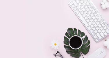 scrivania da ufficio minimale vista dall'alto del tavolo con tastiera del computer, mouse, penna bianca, foglia di monstera, fiori di cotone, bicchieri su un tavolo rosa con spazio di copia, composizione sul posto di lavoro di colore rosa, disposizione piatta