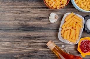 Vista dall'alto di diversi macaroni come ziti rotini e altri con aglio burro fuso sale e ketchup su sfondo di legno con spazio di copia