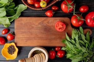 Vista dall'alto di verdure come pomodoro e foglie di menta verde con semi di pepe nero e frantoio per aglio e tagliare il pomodoro sul tagliere su sfondo di legno