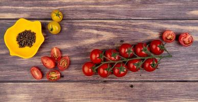 vista dall'alto di pomodori con semi di pepe nero su fondo in legno foto