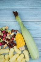 Vista dall'alto di mais tagliato e mais crudo con birilli popcorn e cereali pop di mais su sfondo di legno foto