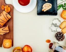 Vista dall'alto del rotolo tagliato e affettato con prugne secche cupcake sul tagliere con marmellata di tè uvetta pesche biscotti e pigna su sfondo bianco con spazio di copia foto