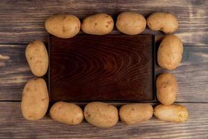 vista dall'alto di patate intorno al vassoio vuoto su sfondo di legno foto