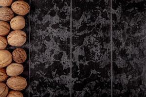 vista dall'alto di noci intere su fondo di legno nero con lo spazio della copia foto