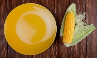 vista dall'alto della pannocchia di mais con guscio e piatto giallo vuoto su fondo in legno