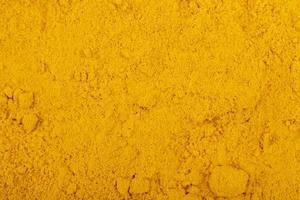 vista dall'alto di curcuma in polvere sfondo e consistenza foto