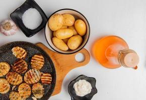 Vista dall'alto di fette di patate fritte in padella sul tagliere con quelle crude nella ciotola aglio burro fuso maionese sale e pepe nero su sfondo bianco