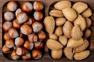 vista dall'alto di noci nocciole con mandorle in guscio su un vassoio di legno