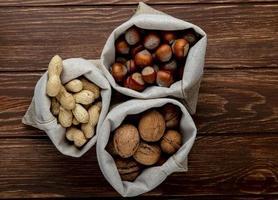 vista dall'alto di noci in sacchi noci arachidi e nocciole in guscio su sfondo di legno