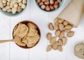 vista dall'alto di burro di arachidi in una ciotola e mandorle in guscio sparse su sfondo bianco