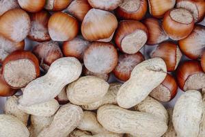 vista dall'alto di noci miste in guscio di nocciole e arachidi su sfondo bianco