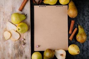 Vista dall'alto del taccuino di carta artigianale incorniciato con pere fresche mature e un tagliere di legno con coltello da cucina e fette di pere su sfondo nero foto