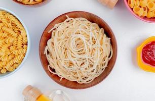 vista dall'alto di macaroni come spaghetti rotini e pipe-rigate con ketchup su sfondo bianco