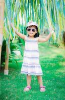 ritratto di cute bambina asiatica indossare occhiali da sole e cappello nel parco