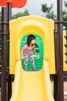 bambina divertendosi a giocare a cursore nel parco giochi in estate foto