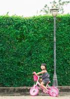 bambina felice andare in bicicletta nel parco