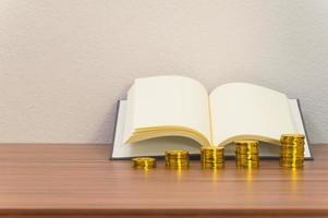 pile di libri e monete sulla scrivania foto