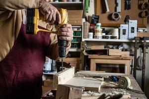 falegname con un trapano giallo che fa un buco con un trapano di legno a bordo foto
