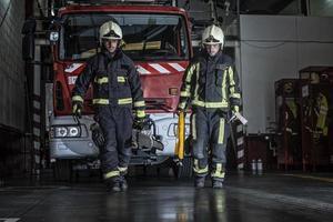 vigili del fuoco in uscita dalla stazione attrezzati e con gli strumenti per l'estinzione dell'incendio foto