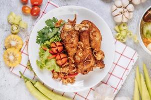 cosce di pollo fritte con pomodoro, peperoncino, cipolla fritta, lattuga, mais e funghi