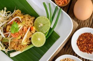 pad thai con limone, uova e condimento su un tavolo di legno