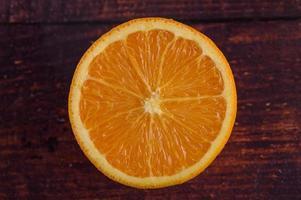 immagine macro di un arancio maturo su uno sfondo di legno