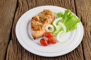 pollo alla griglia su un piatto con pomodori, insalata e cipolla