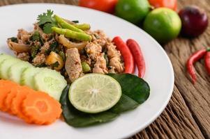 insalata di maiale macinata con spezie su un tavolo di legno