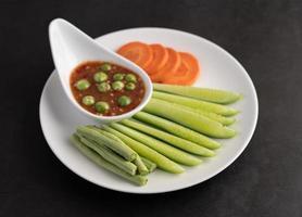 salsa di pasta di gamberetti in una ciotola con cetriolo, fagioli lunghi e carote