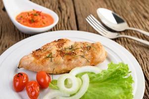 pollo alla griglia su un tavolo di legno con pomodori, insalata, cipolla e salsa di peperoncino