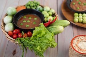 pasta di pasta di peperoncino in una ciotola con melanzane, carote, peperoncino e cetrioli in un cestino
