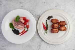 pancetta di maiale avvolta in salsiccia e spezie foto
