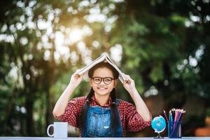 giovane ragazza con il libro sopra la sua testa nel parco