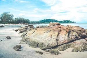 rocce sulla spiaggia con cielo blu nuvoloso