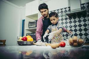 papà insegna a suo figlio come cucinare in cucina foto